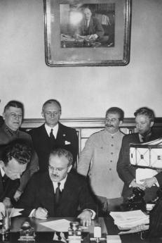 Sovětský ministr zahraničí Vjačeslav Molotov, za ním německý ministr zahraničí Joachim von Ribbentrop a sovětský vůdce Josif Vissarionovič Stalin